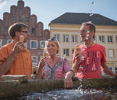 Drei Personen essen ein Eis an einem Brunnen
