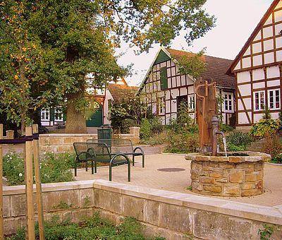 Blick auf den Ort von Hilter mit Brunnen und Sitzbank