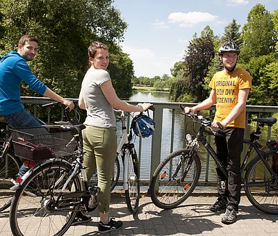 Drei Personen stehen mit ihren Fahrrädern auf einer Brücke